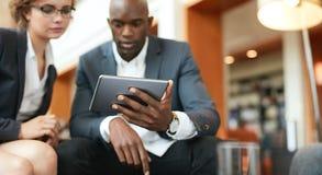 Businesspeople som sitter tillsammans genom att använda den digitala minnestavlan Arkivbild