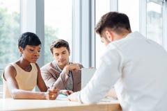 Businesspeople som tillsammans sitter på tabellen och arbete i konferensrum royaltyfria bilder