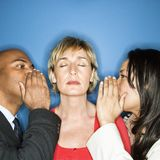 Businesspeople spreading rumors. Businesspeople whispering into each ear of businesswoman royalty free stock image