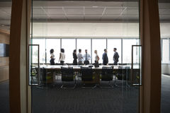 Businesspeople Stand And Chat Before Meeting In Boardroom royalty free stock photography