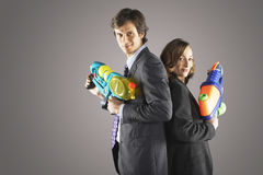 Businesspeople Standing Back To Back With Water Guns Stock Image
