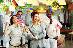 Businesspeople standing with flags in office Royalty Free Stock Images