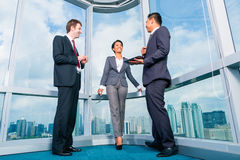 Businesspeople standing at office windo working Stock Photography
