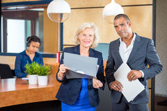 Businesspeople Standing At Reception Counter Stock Photo