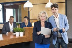 Businesspeople Standing At Reception Counter Royalty Free Stock Photos