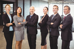 Businesspeople standing together with arms crossed Stock Photos