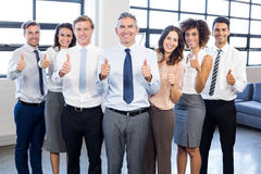 Businesspeople standing together and giving thumbs up Royalty Free Stock Photo