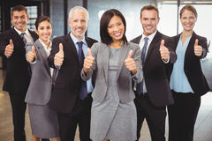 Businesspeople standing together and giving thumbs up Stock Photo