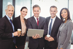 Businesspeople standing together with a laptop Royalty Free Stock Photos
