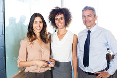Businesspeople standing together in office Stock Photos