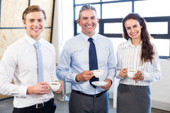Businesspeople standing together in office Royalty Free Stock Photos
