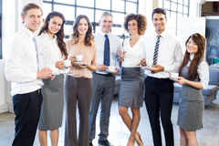 Businesspeople standing together in office Stock Images