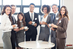 Businesspeople standing together in office Royalty Free Stock Images