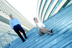 Businesspeople On Steps Of Office Complex. Portrait of two business colleagues outside an office building on steps.  Businessman is walking down steps Stock Photo