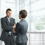 Businesspeople talking. Two young businesspeople talking in office lobby, looking at each other, smiling Royalty Free Stock Image