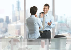 Businesspeople talking. Two businesspeople standing at desk in downtown office building, talking and smiling royalty free stock photos
