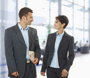 Businesspeople talking. Two happy businesspeople talking in office lobby, looking at each other, smiling Stock Images