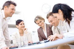 Businesspeople talking. Five business people sitting around table talking and working together, smiling stock images