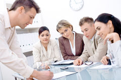 Businesspeople talking. At office, sitting around desk stock photo