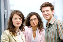 Businesspeople talking. Happy young businesspeople talking in front of office window, smiling, friendship royalty free stock image