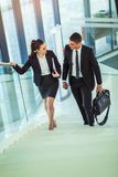 Businesspeople talking as they walk into the office. Two businesspeople talking and smiling as they walk into the office royalty free stock photography