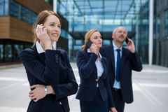 Businesspeople talking on mobile phones Royalty Free Stock Images