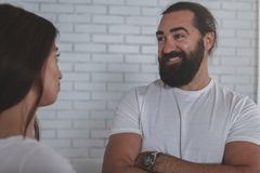Businesspeople talking at the office. Charming mature businessman laughing, talking to female colleague at work. Happy bearded men enjoying working with his stock images