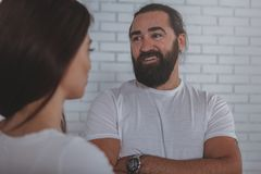 Businesspeople talking at the office. Handsome cheerful mature businessman smiling joyfully, talking to his female colleague. Happy bearded men enjoying chatting stock image