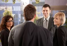 Businesspeople talking outdoor. Group of young businesspeople talking in front of of office building royalty free stock images