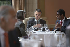 Businesspeople Talking At Restaurant Table Stock Photography