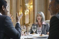 Businesspeople Talking At Restaurant Table Stock Photo