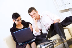 Businesspeople teamworking. Businesspeople sitting on sofa at office and working together on laptop computer stock photography