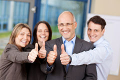 Businesspeople With Thumbs Up Sign In Office Royalty Free Stock Image
