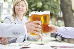 Businesspeople toasting beer glasses at outdoor restaurant Stock Photography