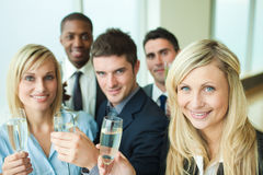 Businesspeople toasting with champagne. Business people toasting with champagne in an office Royalty Free Stock Image