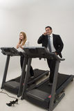 Businesspeople on a Treadmill - Vertical. Male and female businesspeople jogging on a treadmill while talking on their phones Royalty Free Stock Photography