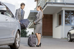 Businesspeople unloading luggage from car outside hotel Stock Photo
