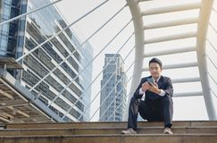 Businesspeople use cell phones to sit on a desk in the city. Con stock photography