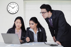 Businesspeople use laptop with clock in office Stock Photography
