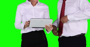 Businesspeople use a tablet computer in meeting. Two anonymous businesspeople shaking hands and using a tablet computer in a meeting while standing in the studio stock footage