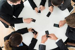 Businesspeople using cell phone. Group Of Businesspeople Using Cell Phone Sitting At Table stock image