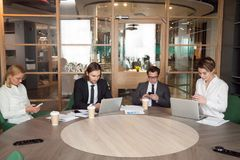 Businesspeople using devices during company business meeting stock images