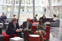 Businesspeople Using Digital Devices In Busy Office Lobby Royalty Free Stock Photo