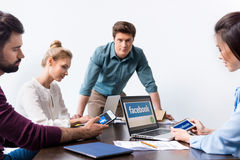Businesspeople using digital devices with facebook logo icons on screens. Young businesspeople using digital devices with facebook logo icons on screens stock photos