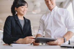 Businesspeople using digital tablet in office Stock Photo