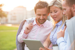 Businesspeople using digital tablet at park on sunny day Royalty Free Stock Photos