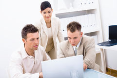 Businesspeople using laptop. Group of young businesspeople working together in office, using laptop computer stock image