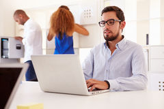 Businesspeople Using Laptop In Office Of Start Up Business Stock Photos