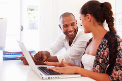 Businesspeople Using Laptop In Office Of Start Up Business Stock Photography