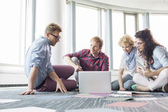 Businesspeople using laptop while sitting on floor at creative office Stock Photo